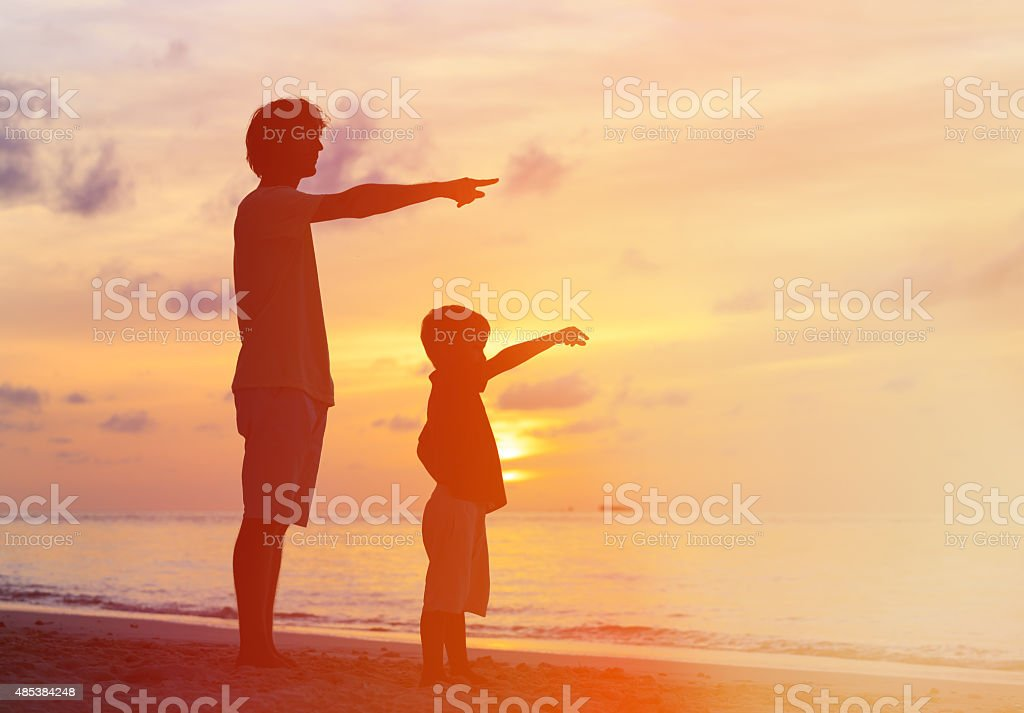 father and son at sunset beach, pointing to the sun stock photo