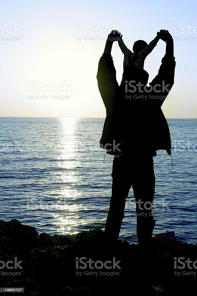father and son at sunset sea royalty-free stock photo