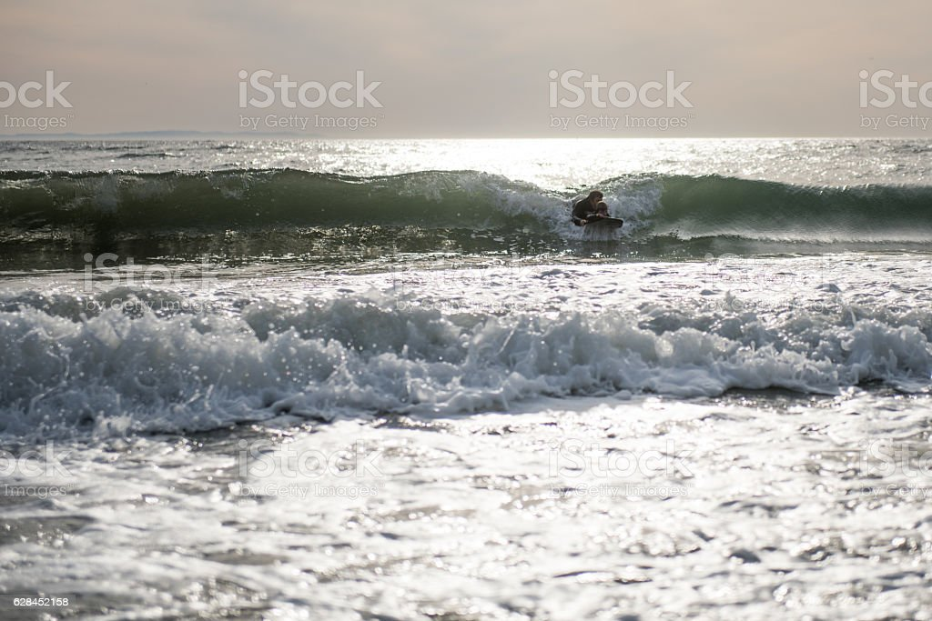 Father and son boogie boarding together stock photo