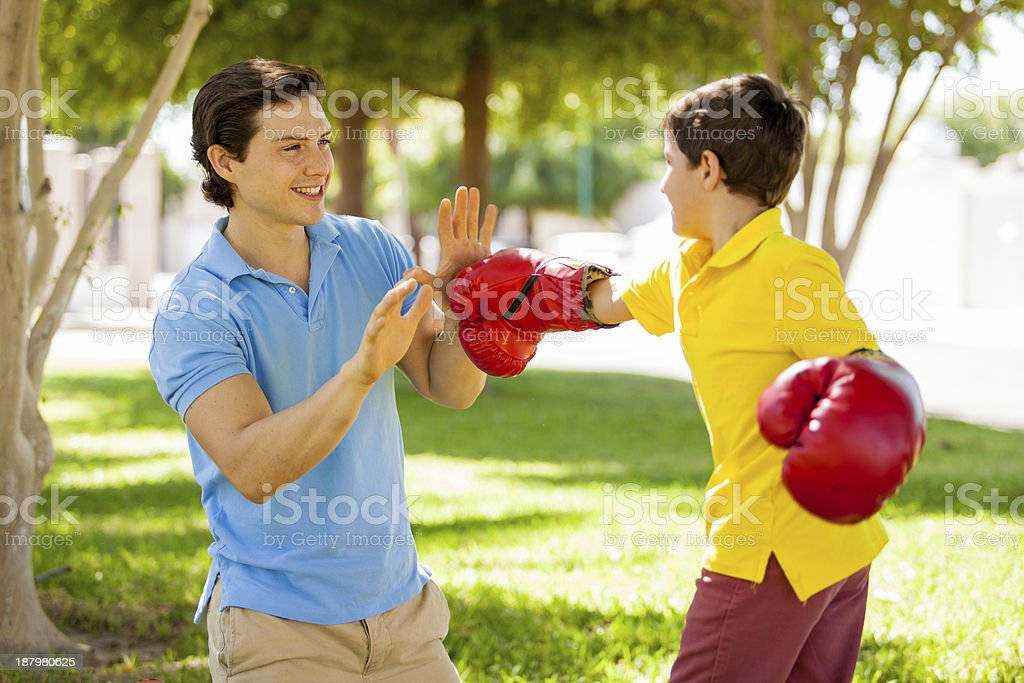 Father and son boxing outdoors stock photo