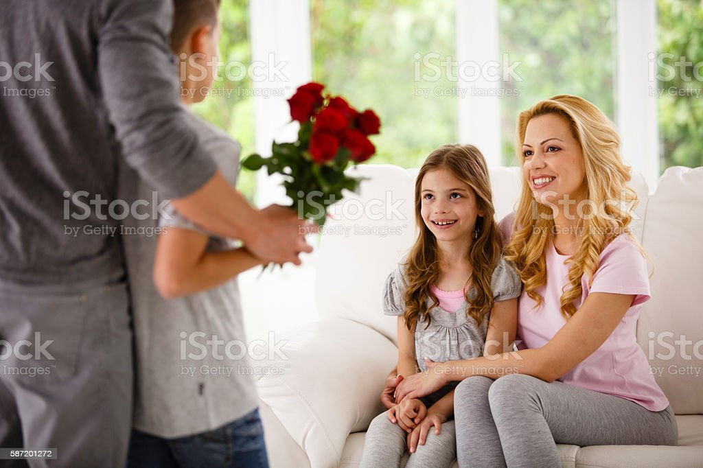 Father and son bringing roses for family stock photo
