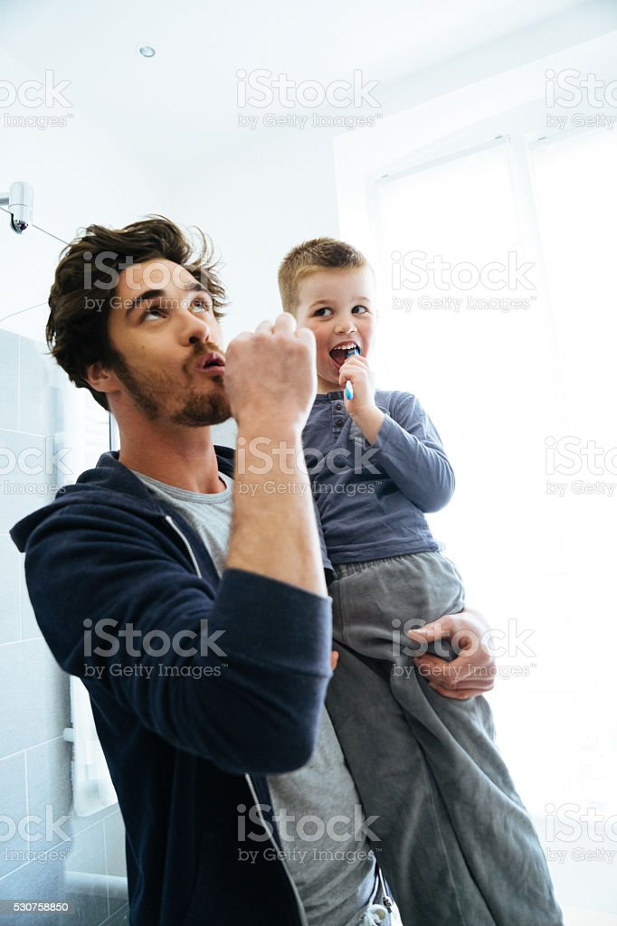 Father And Son Brushing Teeth stock photo