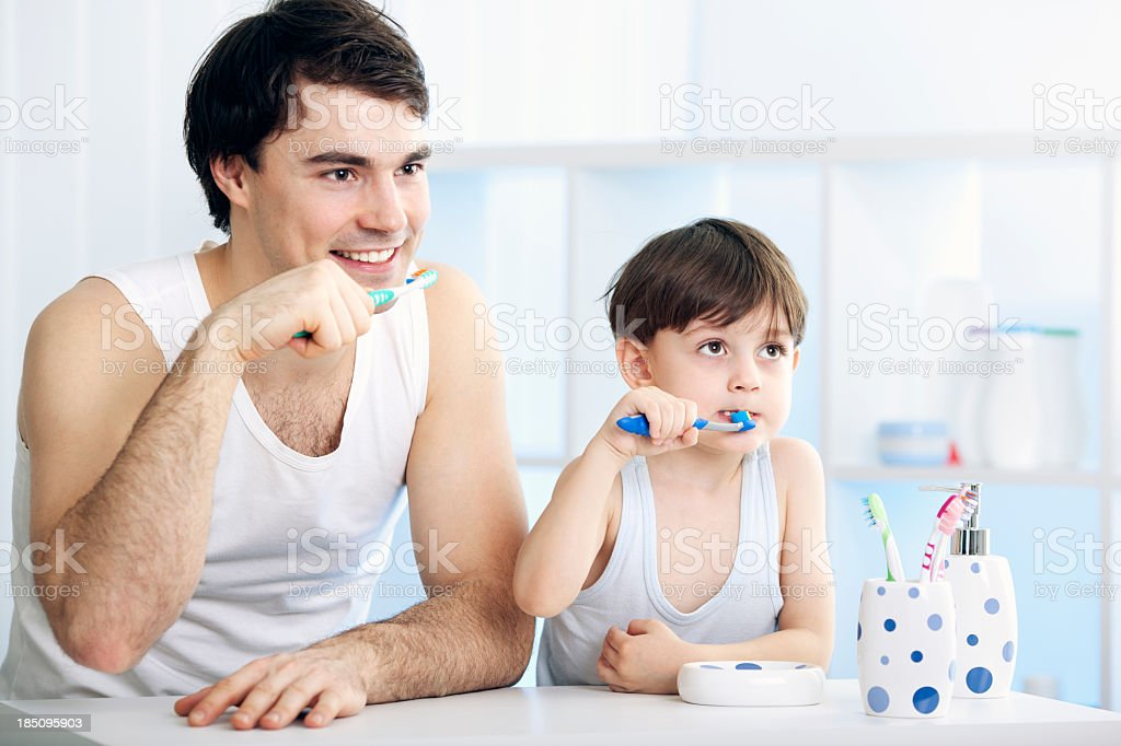 Father and son brushing teeth together royalty-free stock photo