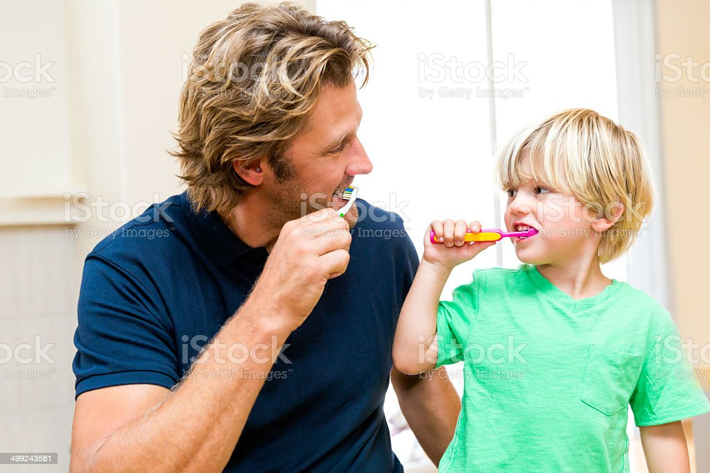 Father and son brushing teeth together. stock photo