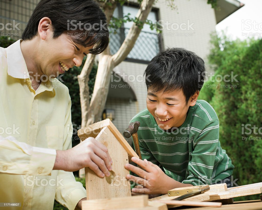 Father and Son Building a Birdhouse royalty-free stock photo