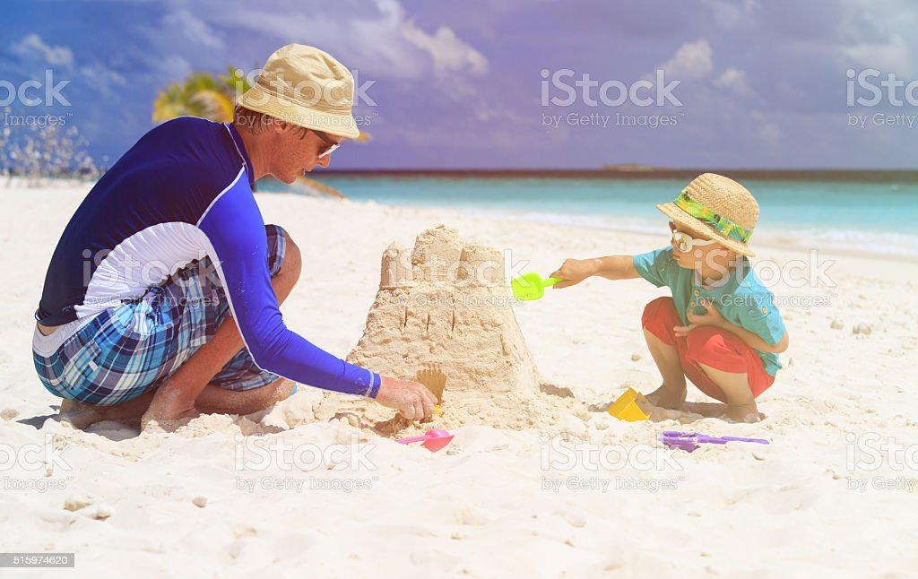 father and son building sand castle on beach stock photo