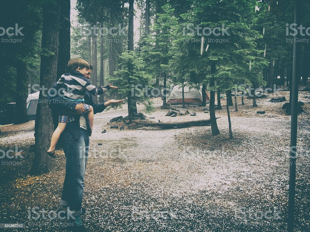 Father and Son camping in a hail storm stock photo