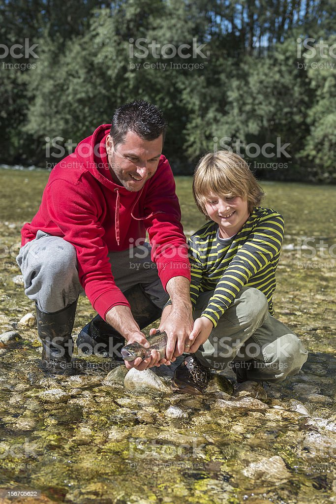 Father and son catch a trout fish stock photo
