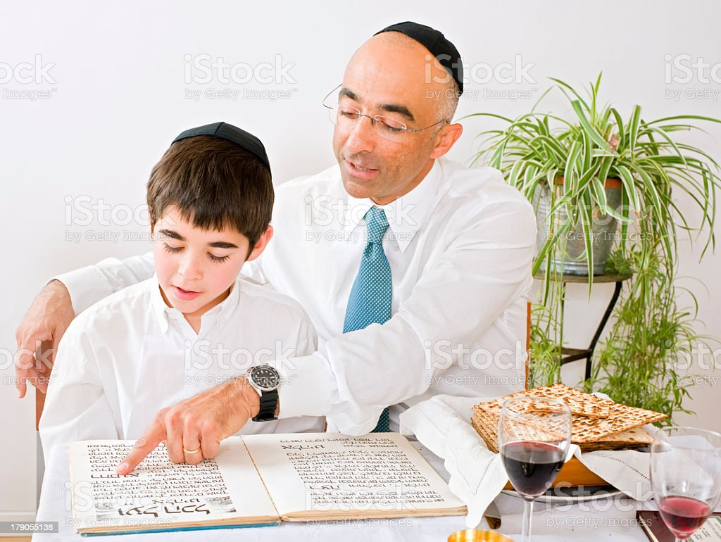 A father and son celebrating Passover and reading stock photo