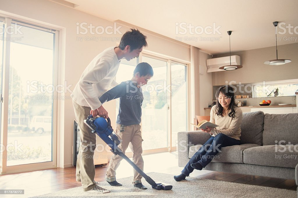 Father and son cleaning with a vacuum cleaner at home. stock photo