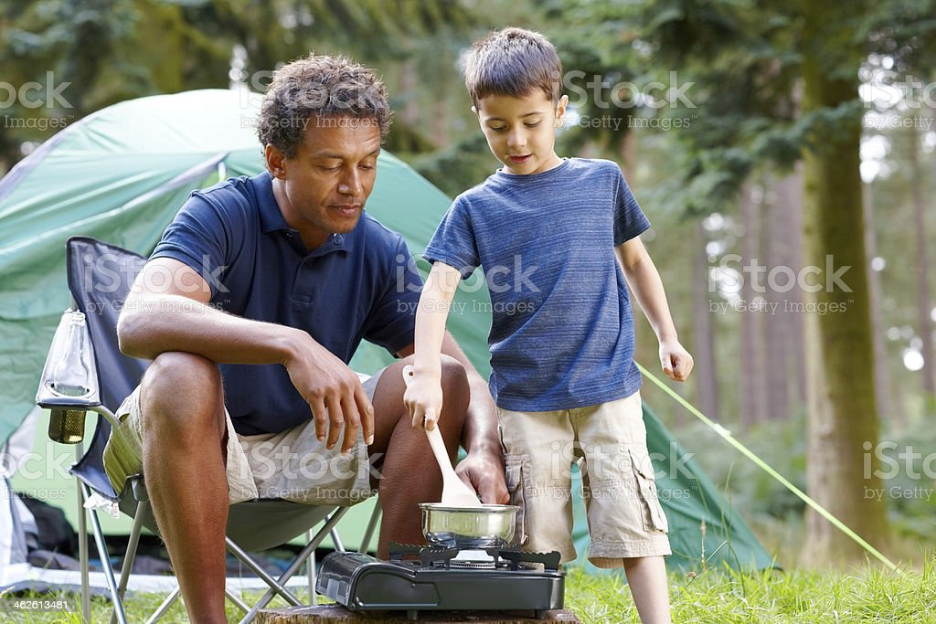 Father and son cooking breakfast on camping holiday stock photo