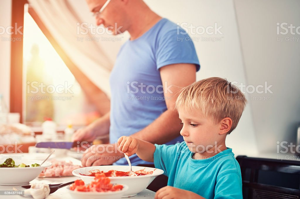 Father and son cooking dinner stock photo