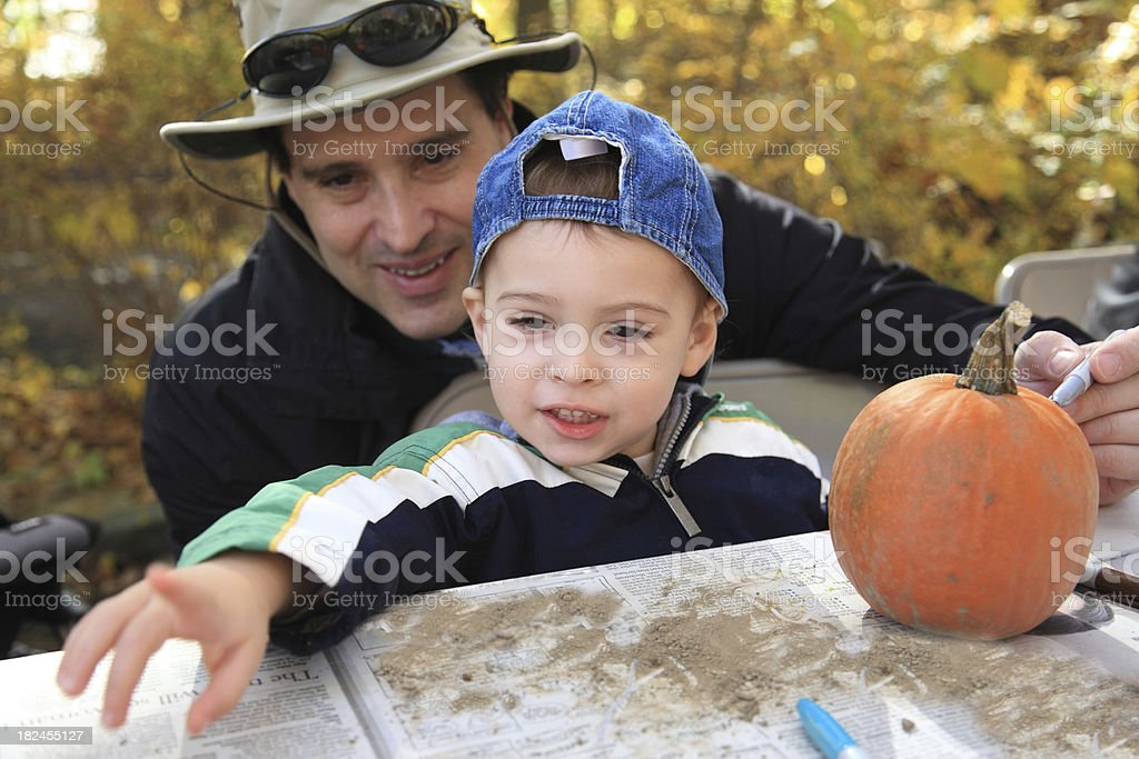 Father and son decorating a pumpkin for Halloween royalty-free stock photo