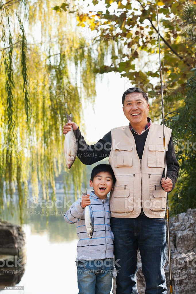 Father and son displaying fishing catch at lake royalty-free stock photo