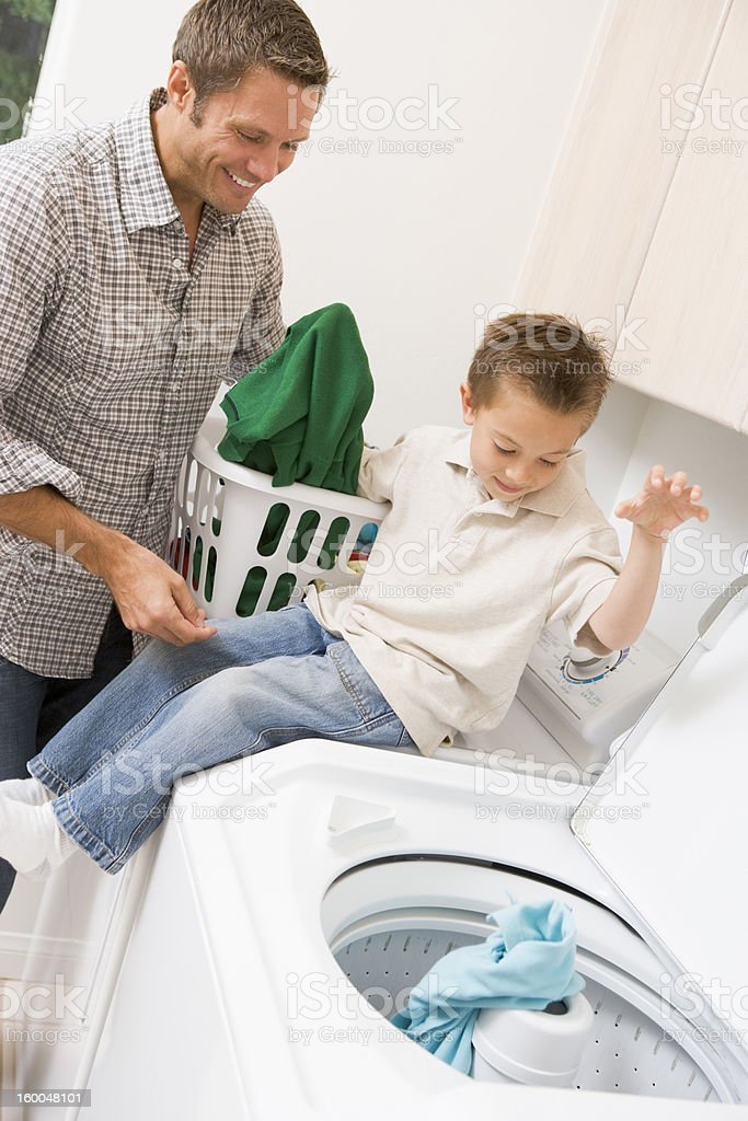 Father And Son Doing Laundry royalty-free stock photo