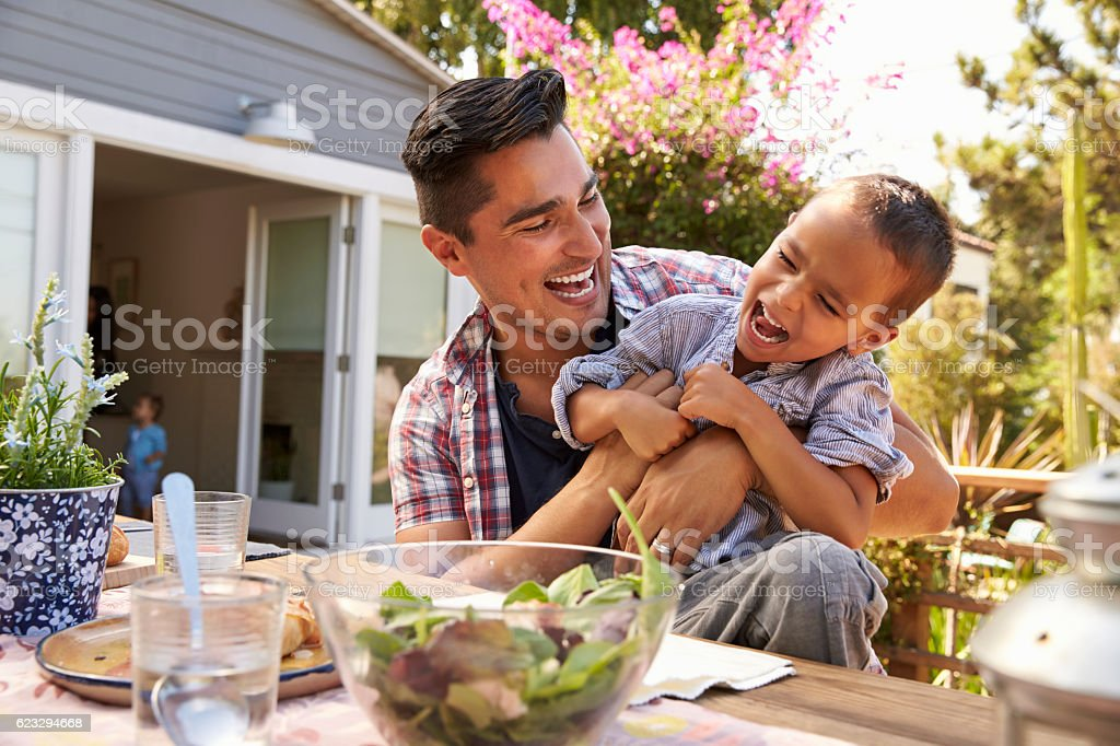 Father And Son Eating Outdoor Meal In Garden Together royalty-free stock photo