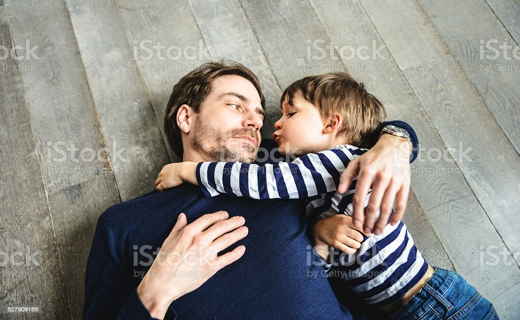 father and son embracing on the floor stock photo
