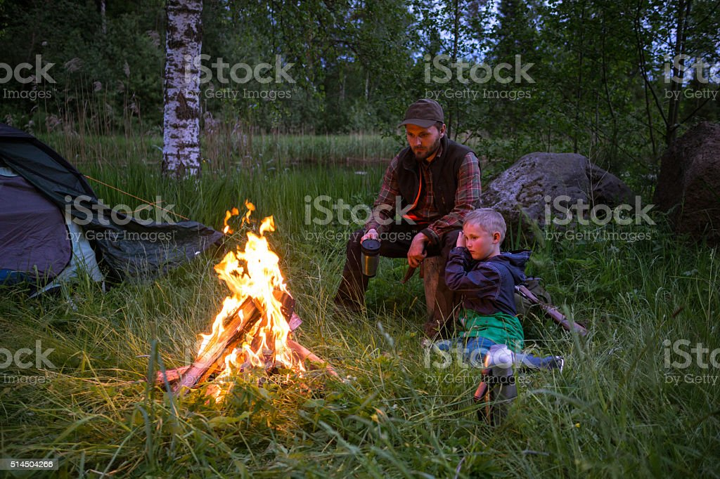 Father and son enjoying a campfire stock photo