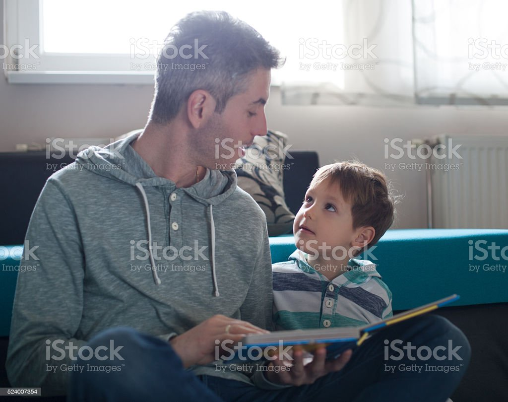 Father and son enjoying at home. stock photo