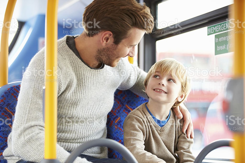 Father And Son Enjoying Bus Journey Together stock photo