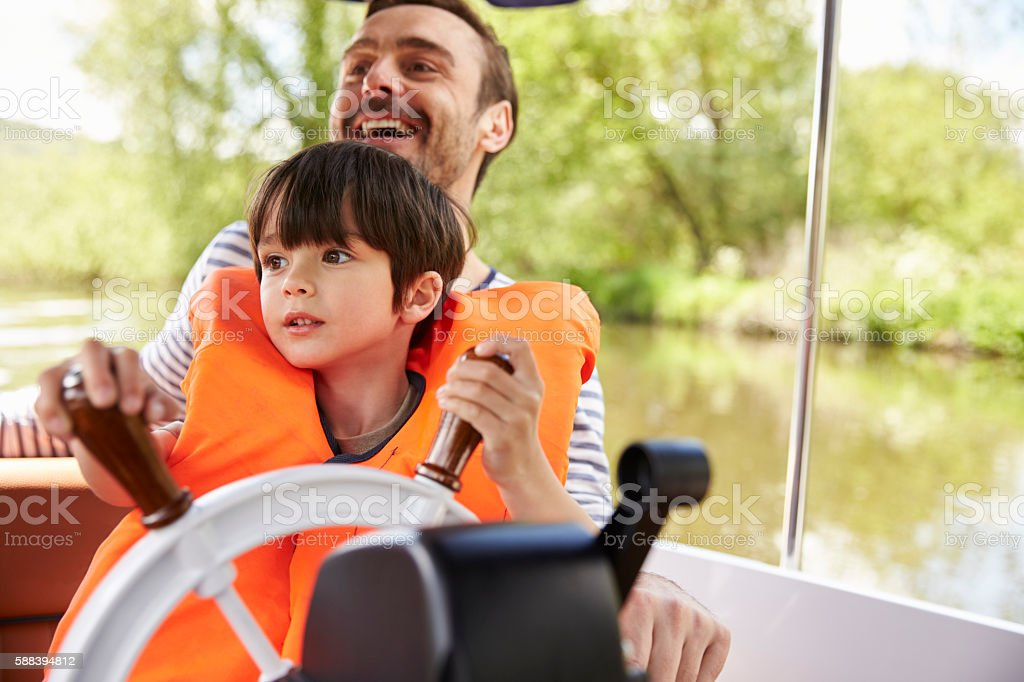 Father And Son Enjoying Day Out In Boat On River Together stock photo