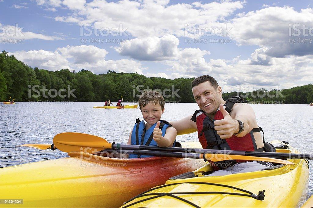 Father and son enjoying kayaking stock photo