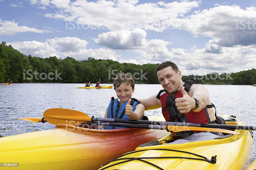 Father and son enjoying kayaking stock photo