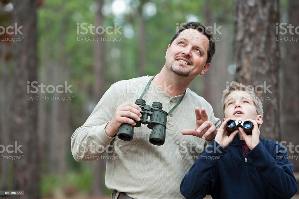 Father and son enjoying scenic view with binoculars stock photo