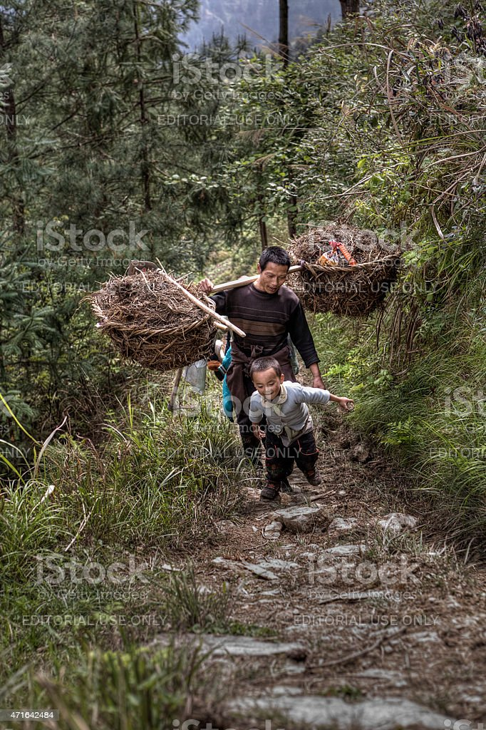 Father and son farmers returning from field work, rural China. stock photo