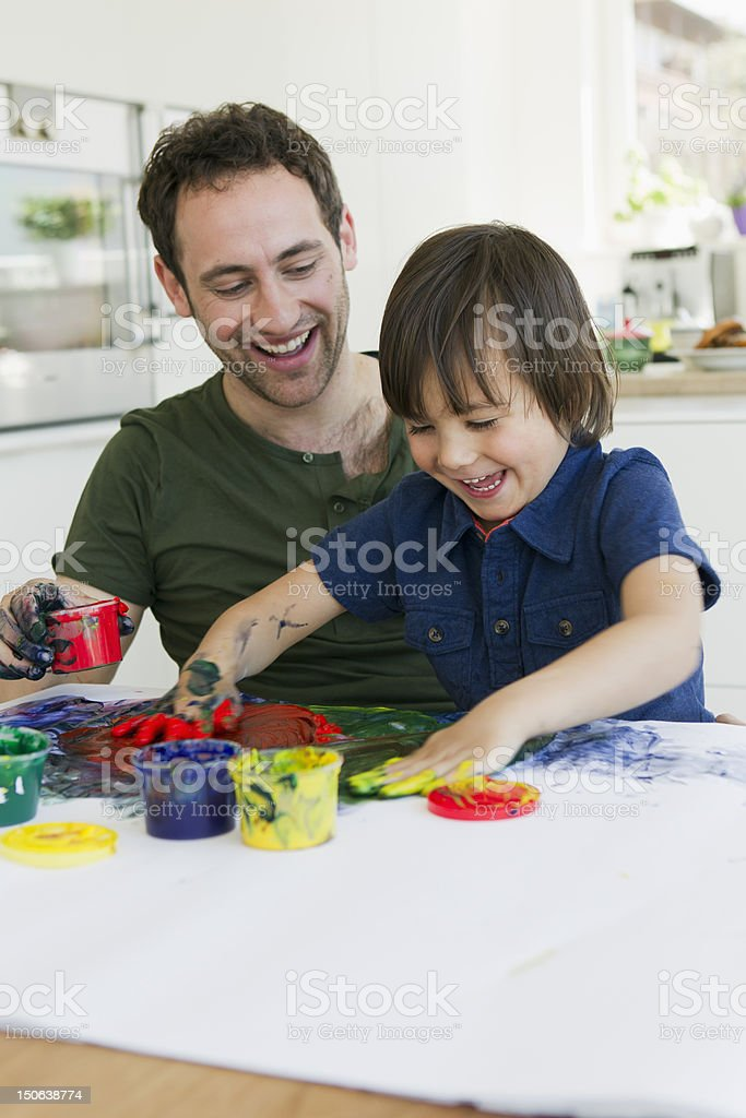 Father and son finger painting together stock photo