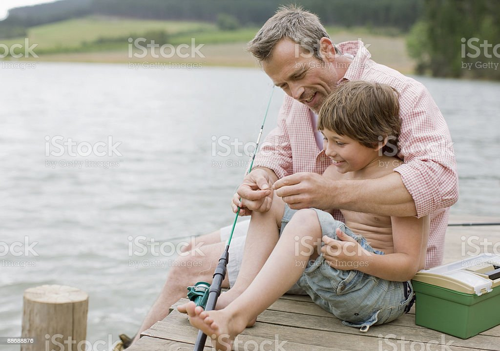 Father and son fishing off pier at lake royalty-free stock photo