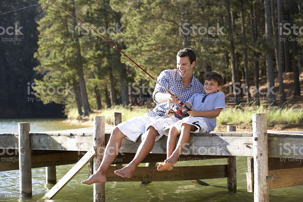A father and son fishing on a lake stock photo