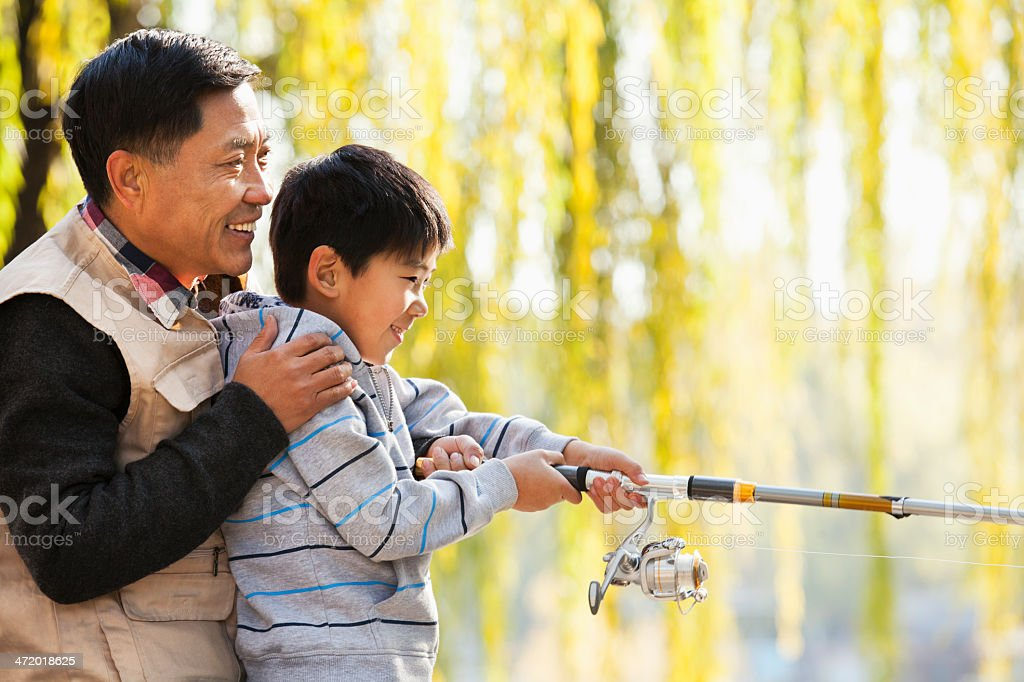 Father and son fishing together at lake royalty-free stock photo
