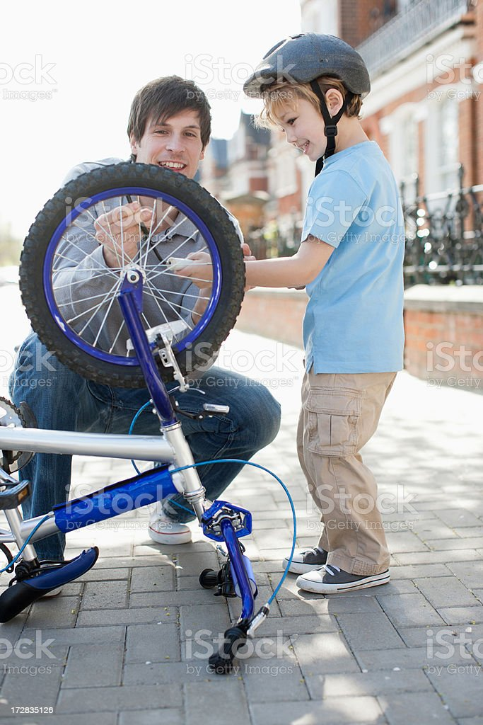 Father and son fixing bicycle tire on sidewalk stock photo