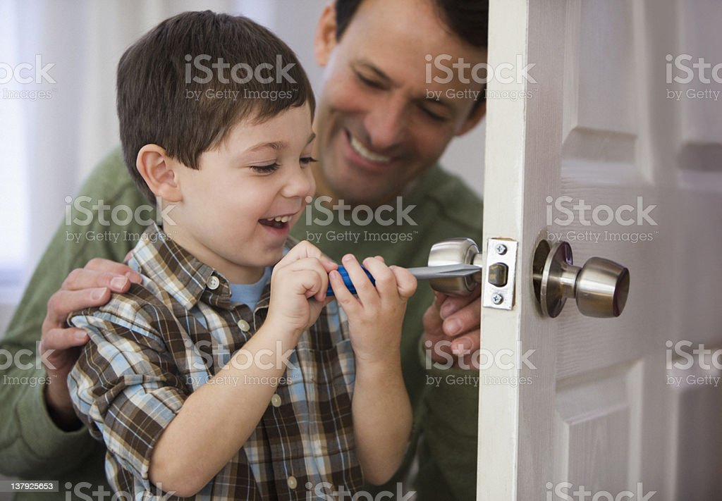 Father and son fixing doorknob stock photo