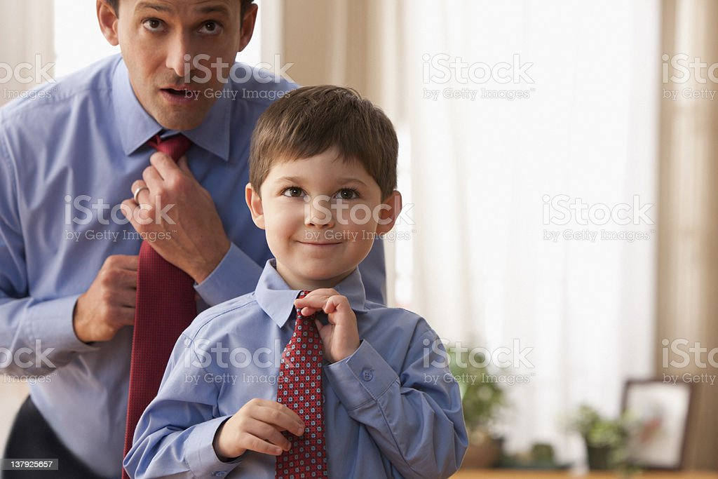 Father and son fixing ties together stock photo
