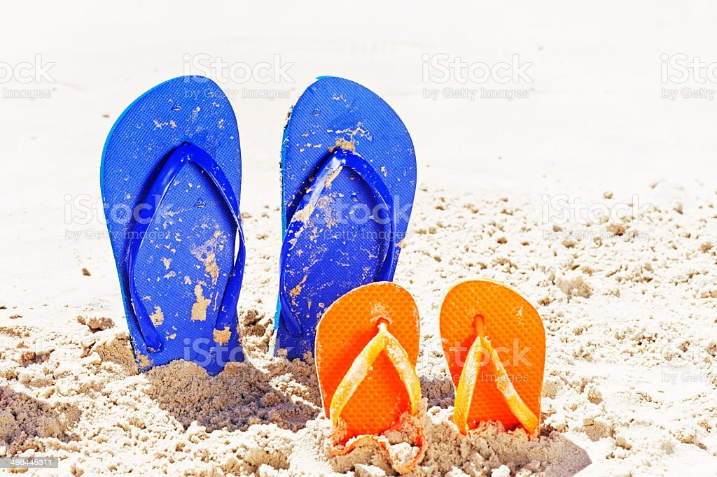 Father and son flipflops on beach. It's vacation time! stock photo