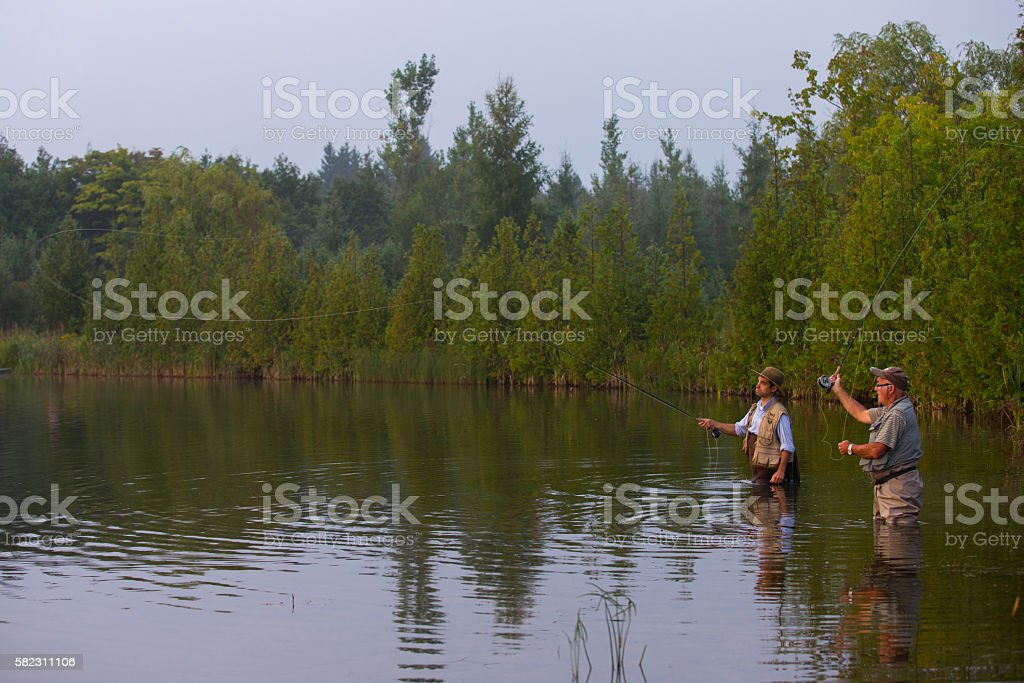 Father and son flyfishing at sunrise stock photo