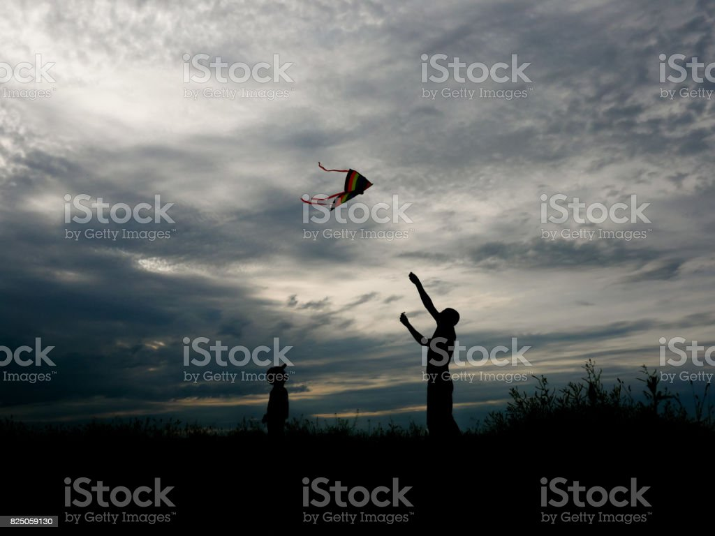 father and son flying a kite at wonderful sunset stock photo