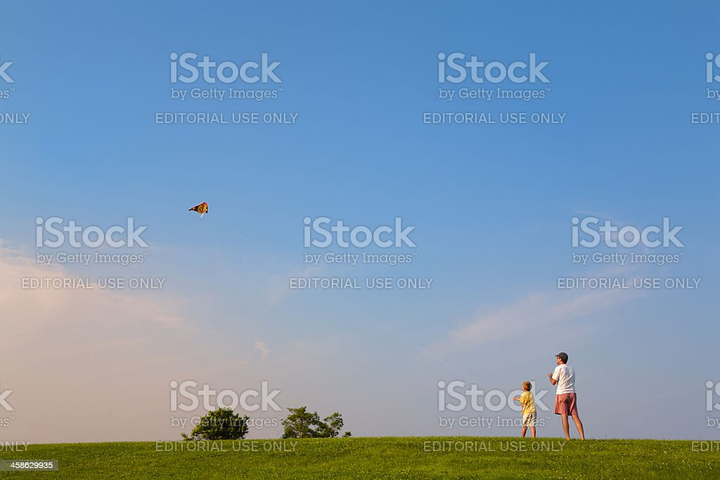 father and son flying kite royalty-free stock photo