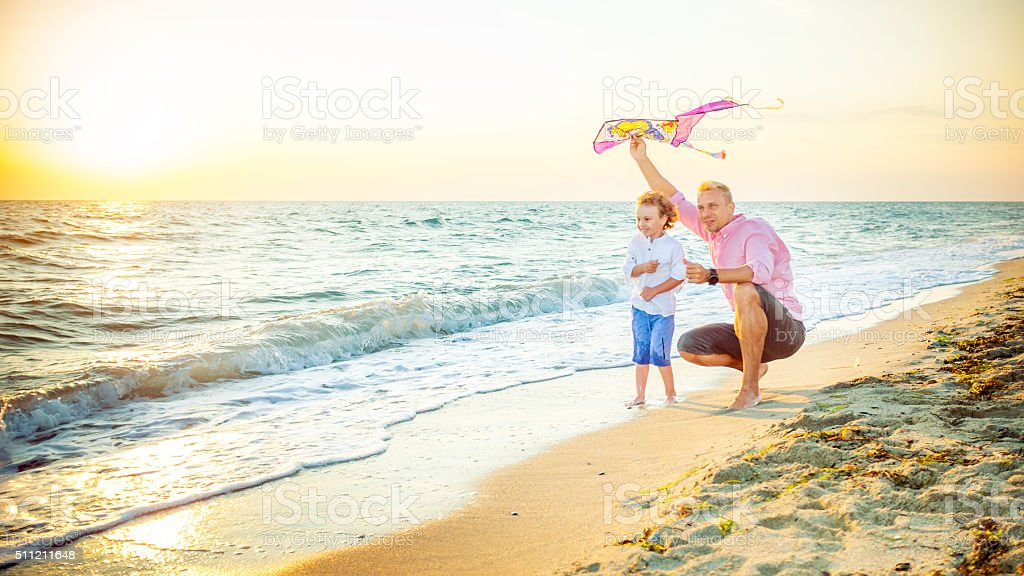Father and son flying kites at the beach stock photo