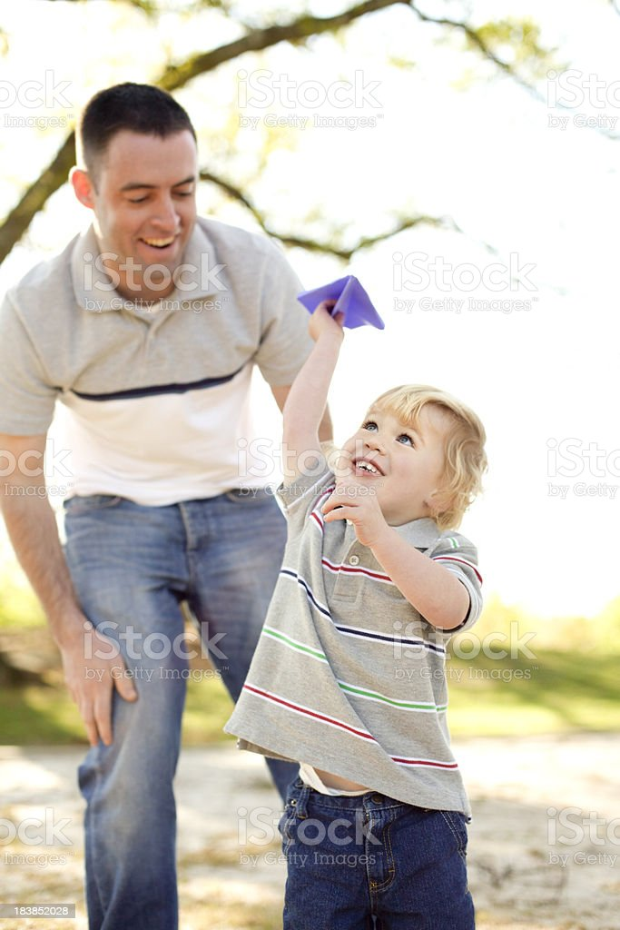 Father and son flying paper airplane royalty-free stock photo