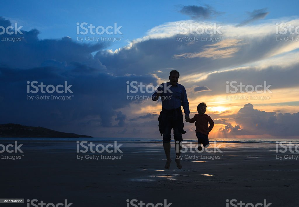 father and son  have fun on the  beach stock photo