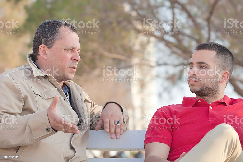 Father and son having discussion on a park bench stock photo