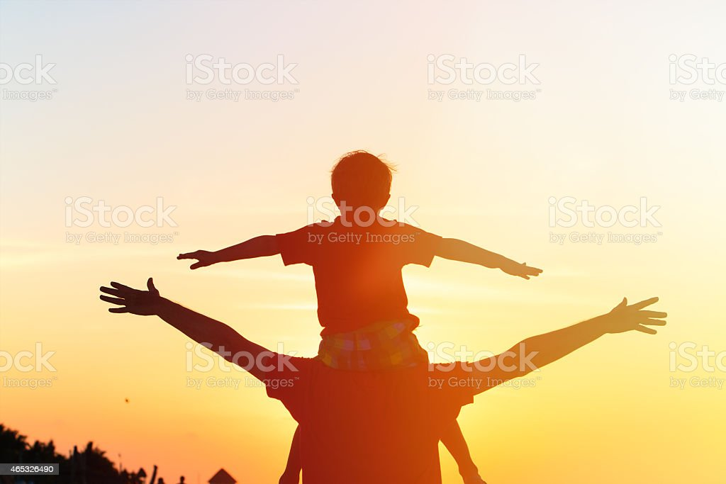 father and son having fun at sunset stock photo