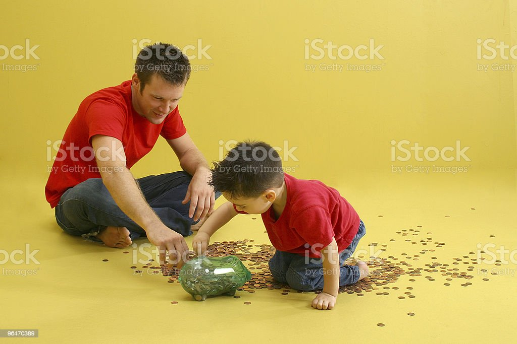 Father and son having fun counting coins from piggy bank stock photo