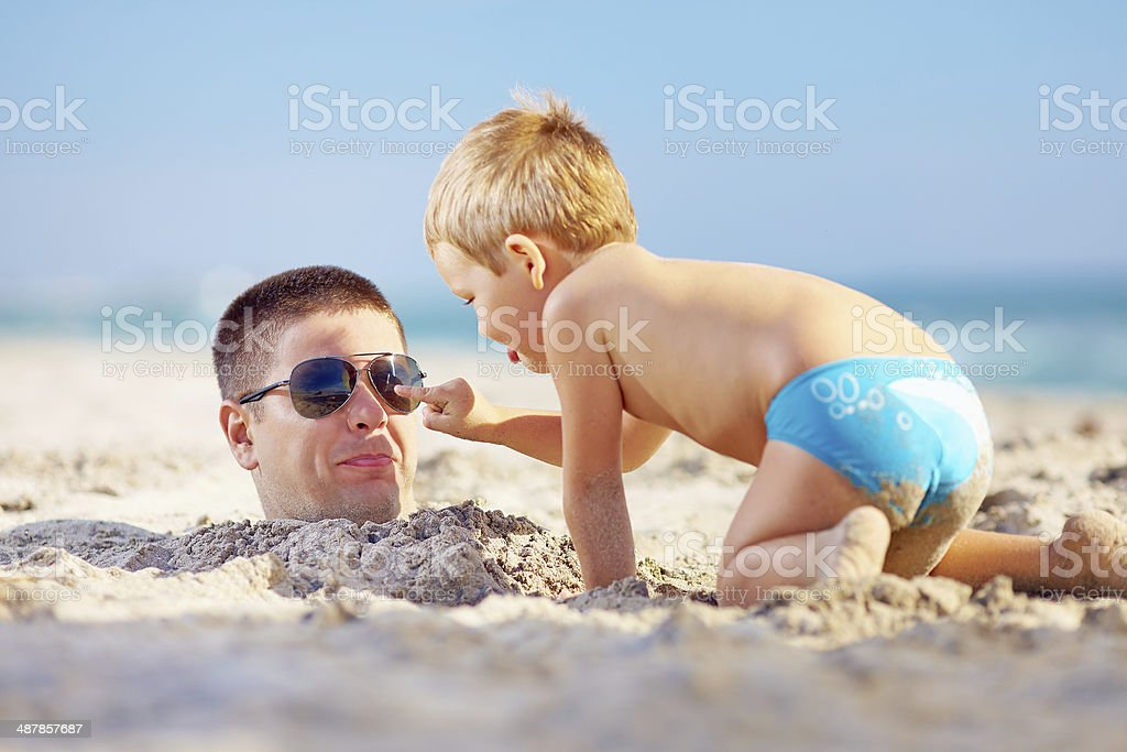 father and son having fun in sand on the beach stock photo