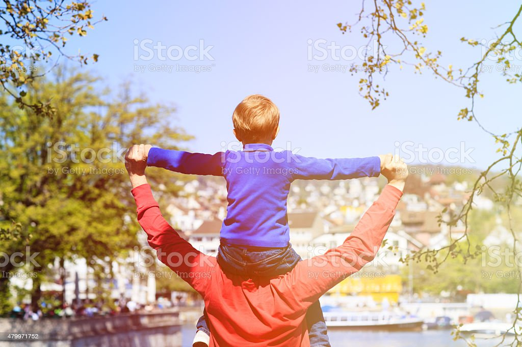 father and son having fun in spring city stock photo