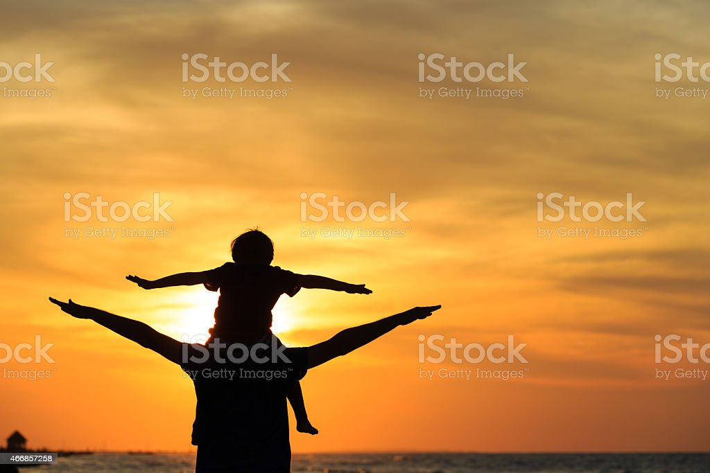 father and son having fun on sunset stock photo