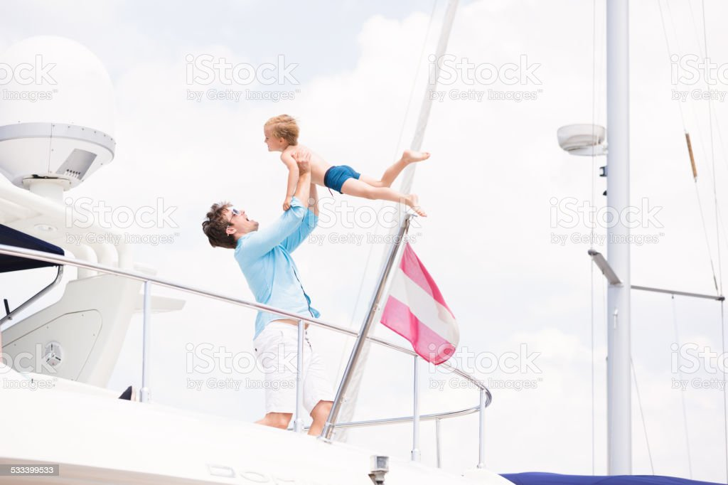 father and son having fun on their yacht stock photo
